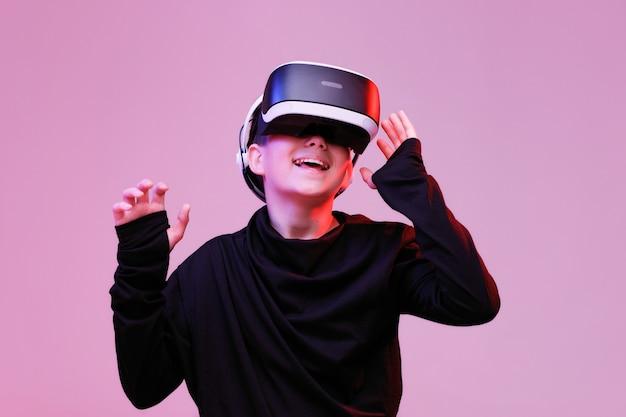 Jonge gelukkige jongen in een bril van virtual reality op neon achtergrond