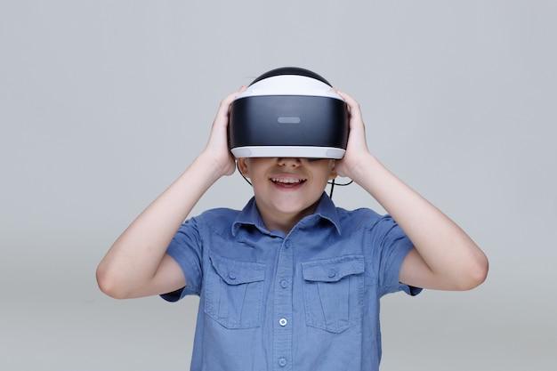 Jonge gelukkige jongen in glazen van virtual reality op grijze achtergrond