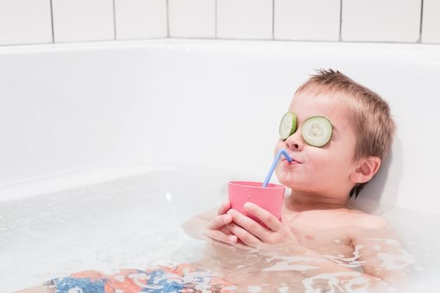 Jonge gelukkige jongen met een rustgevend bad in een bubbelbad, sap drinken