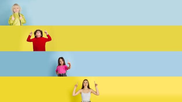 Jonge gelukkige kaukasische kinderen gebaren geïsoleerd op veelkleurige studio achtergrond. menselijke emoties