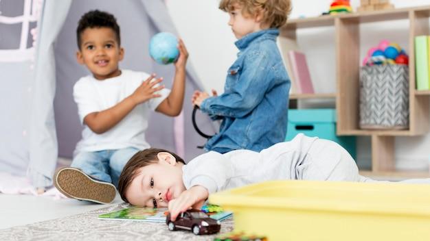 Jonge gelukkige kinderen spelen met speelgoed
