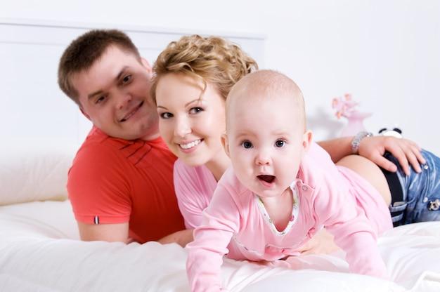 Jonge gelukkige leuke familie met baby liggend op bed thuis