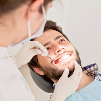 Jonge gelukkige man en vrouw in een tandonderzoek bij tandarts