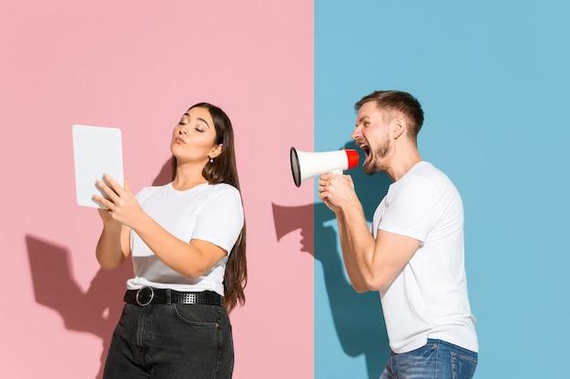 Jonge, gelukkige man en vrouw in vrijetijdskleding op roze, blauwe tweekleurige achtergrond.