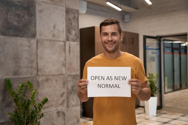 Jonge gelukkige man kantoormedewerker die papier toont met tekst open als nieuw normaal op camera en glimlacht
