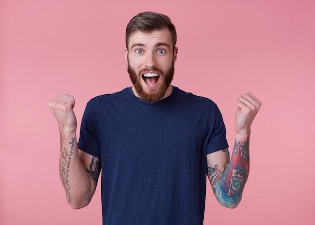 Jonge gelukkige man met rode baard met blauwe ogen, wijd open mond van genot, viert de overwinning van zijn favoriete voetbalteam, met opgeheven armen en gebalde vuisten, geïsoleerd op roze achtergrond.