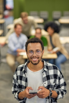 Jonge gelukkige man van gemengd ras die smartphone vasthoudt en naar de camera glimlacht terwijl hij in coworking staat