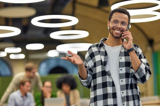 Jonge gelukkige man van gemengd ras die telefonisch praat en glimlacht terwijl hij in een coworking-ruimte staat