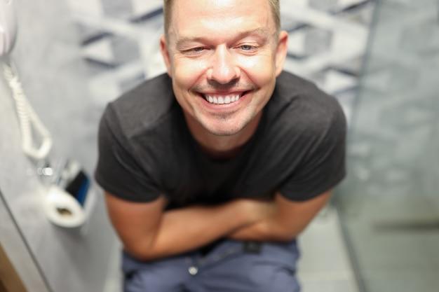 Jonge gelukkige man zittend op het toilet en glimlachen