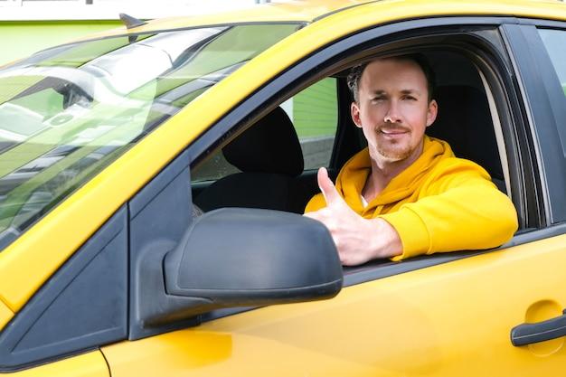 Jonge gelukkige mannelijke taxichauffeur zit achter het stuur van een taxi en laat zien zoals