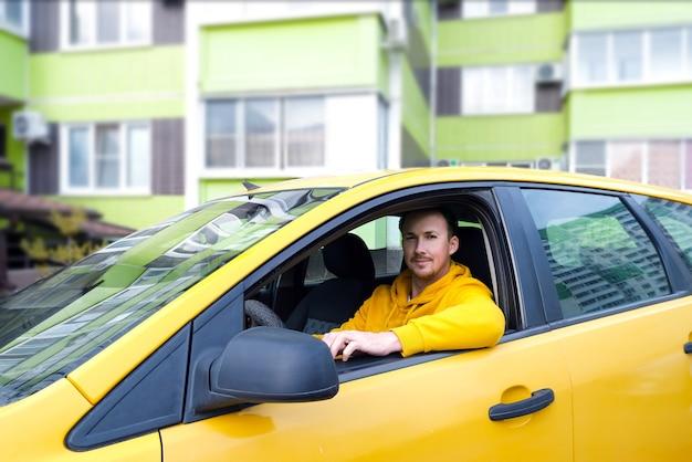Jonge gelukkige mannelijke taxichauffeur zit achter het stuur van een taxi