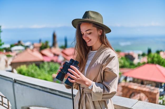 Jonge gelukkige meisjesreiziger die hoed met verrekijker draagt tijdens de reis van het vakantieweekend op een heldere zonnige dag