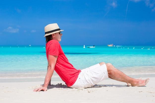Jonge gelukkige mens die de zomer van vakantie op tropisch strand geniet