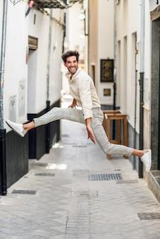 Jonge gelukkige mens die in de straat springt.