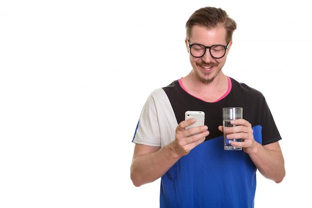 Jonge gelukkige mens gebruikend mobiele telefoon en houdend glas water