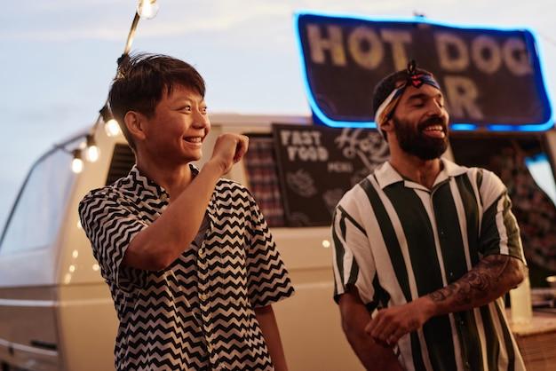 Jonge gelukkige mensen dansen samen tijdens strandfeest