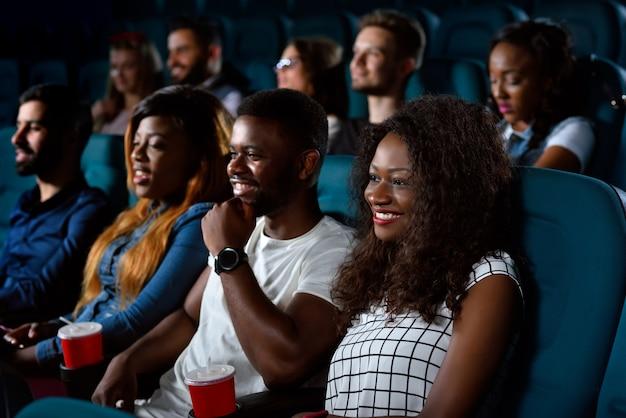 Jonge gelukkige mensen die vreugdevol glimlachen terwijl ze samen naar een film kijken in de plaatselijke bioscoop