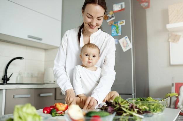Jonge gelukkige moeder die voedsel in de keuken kookt en voor de baby zorgt