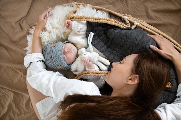 Jonge gelukkige moeder en een slapende baby in een rieten wieg in een warme gebreide muts onder een warme deken met een speeltje in het handvat.