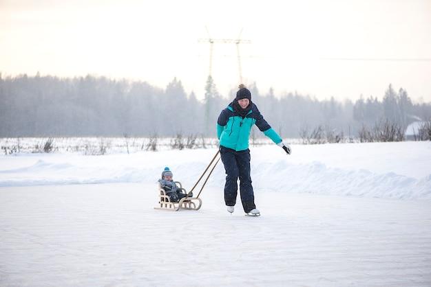 Jonge gelukkige moeder en zoontje van de babyjongen samen sleeën op het besneeuwde wintermeer