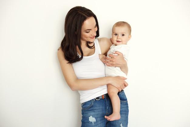 Jonge gelukkige moeder het glimlachen holding die haar babydochter bekijken over witte muur.