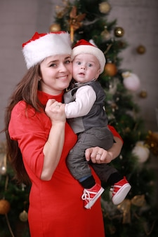 Jonge gelukkige moeder in de hoed van santa hebben een goede tijd met haar zoon thuis in de buurt van de kerstboom.