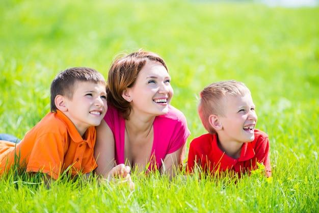 Jonge gelukkige moeder met kinderen in het park