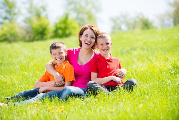 Jonge gelukkige moeder met kinderen in park - openluchtportret