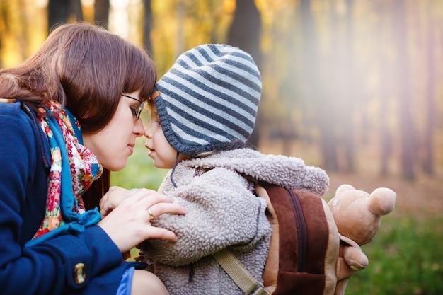 Jonge gelukkige moeder met zoon wandelen in het park