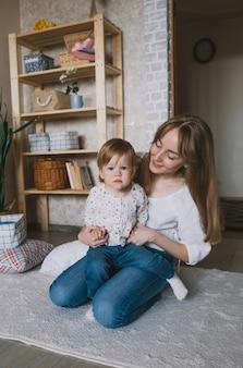Jonge gelukkige moeder speelt met haar dochtertje thuis op de vloer. gezinsgeluk