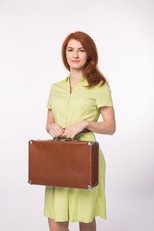 Jonge gelukkige mooie gember vrouw met koffer op witte achtergrond