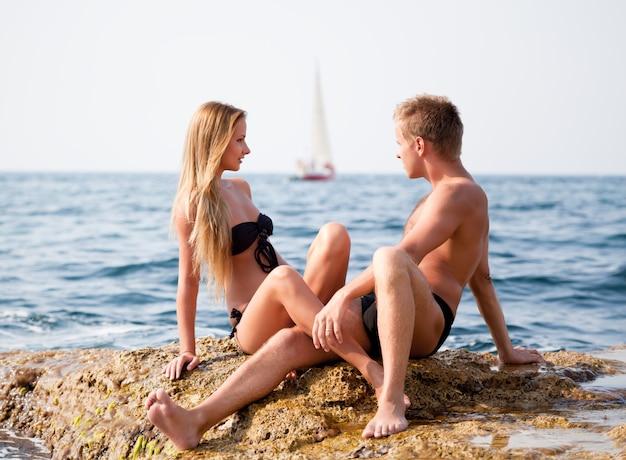 Jonge gelukkige mooie paar vrouw en man zittend op de rotsen en kijken elkaar met zee en jacht op achtergrond op heldere zomerdag