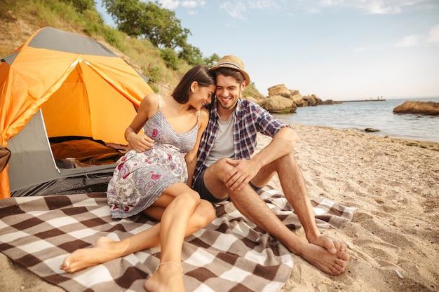Jonge gelukkige mooie paar zitten bij de tent op het strand