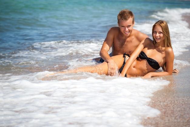 Jonge gelukkige mooie paarvrouw en man die in zeewater met strand bij achtergrond liggen