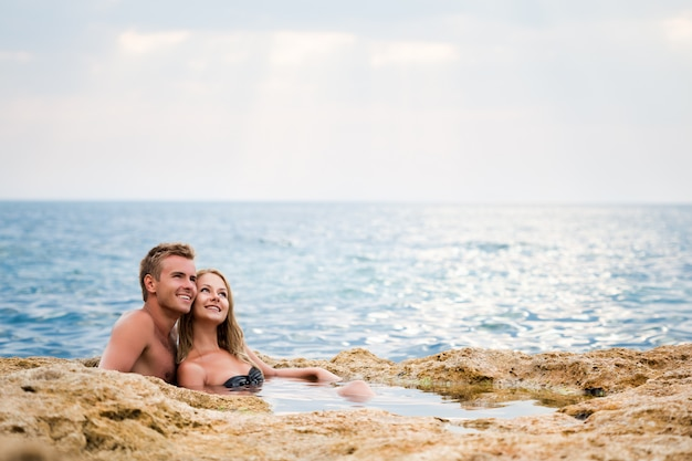 Jonge gelukkige mooie paarvrouw en man zitting in natuurlijke rotspool met water en het glimlachen met overzees