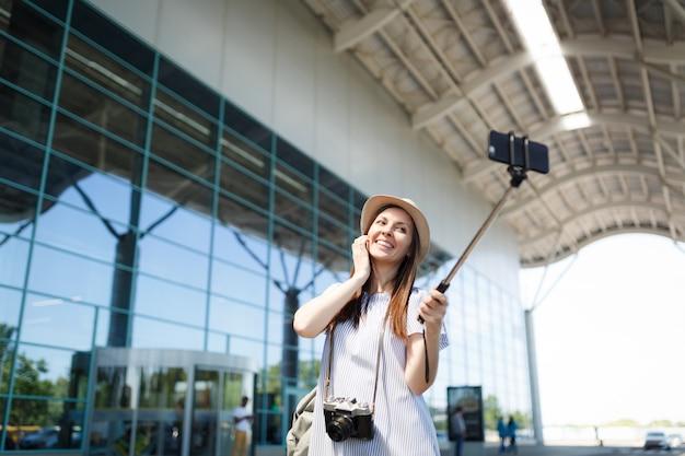 Jonge gelukkige mooie reiziger toeristische vrouw met retro vintage fotocamera doet selfie op mobiele telefoon met monopod egoïstische stok op luchthaven