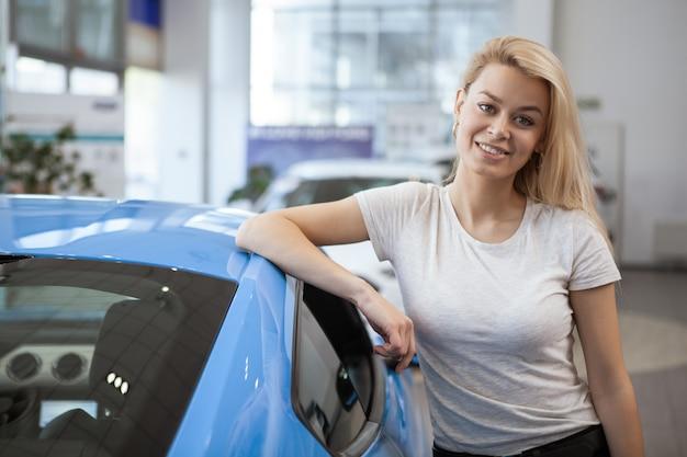 Jonge gelukkige mooie vrouw die na het kopen van nieuwe auto bij het handel drijven glimlachen