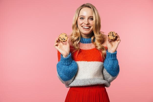 Jonge gelukkige mooie vrouw poseren geïsoleerd over roze muur met zoete koekjes