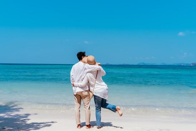Jonge gelukkige moslimpaar witte kleding op kust.