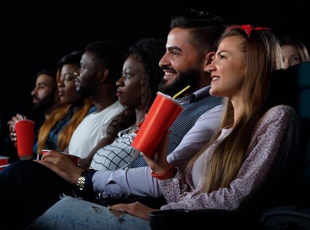 Jonge gelukkige multiculturele vrienden ontspannen in de bioscoop
