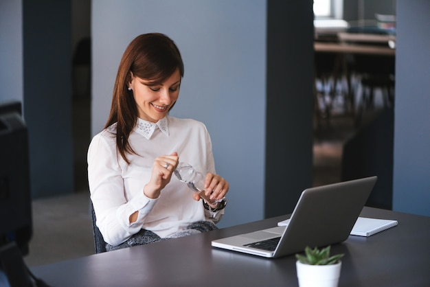 Jonge gelukkige onderneemster die een fles water in bureau houdt