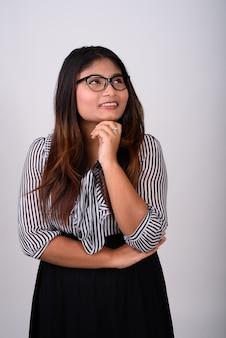 Jonge gelukkige onderneemster die tijdens het denken en het dragen van een bril glimlacht