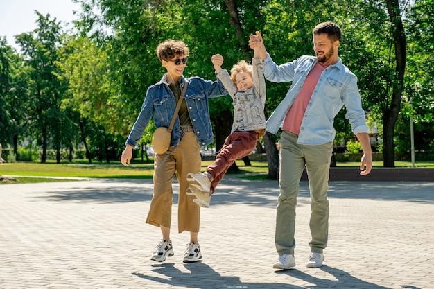 Jonge gelukkige ouders lachen terwijl hun schattige zoontje met de handen vasthoudt en hem over de weg opheft tijdens een wandeling in het openbaar park in de zomer
