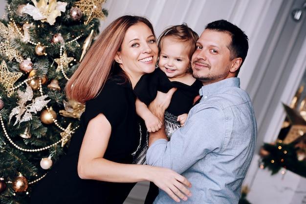 Jonge gelukkige ouders met hun dochtertje samen plezier in de buurt van de kerstboom