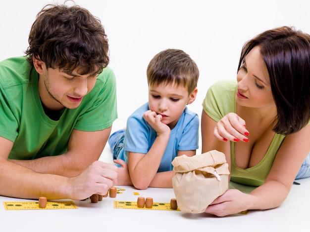 Jonge gelukkige ouders spelen binnenshuis met zoontje