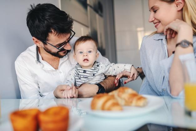 Jonge gelukkige ouders zitten in de eetkamer met hun schattige babyjongen.