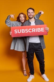 Jonge gelukkige paar bedrijf karton met abonnement inscriptie