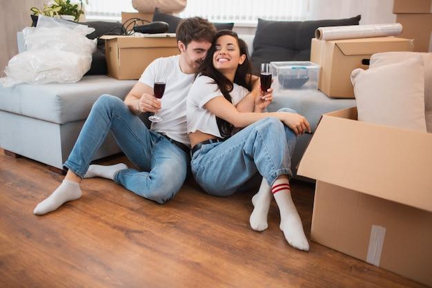 Jonge gelukkige paar drinken van wijn, vieren verhuizen naar een nieuw huis en zitten onder dozen