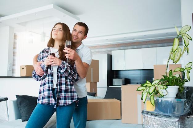 Jonge gelukkige paar drinken van wijn, vieren verhuizen naar een nieuw huis onder dozen.