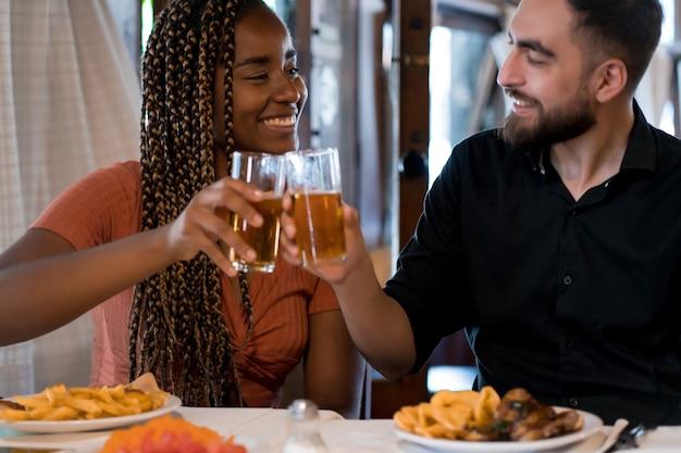 Jonge gelukkige paar genieten van een maaltijd samen terwijl ze een date hebben in een restaurant.
